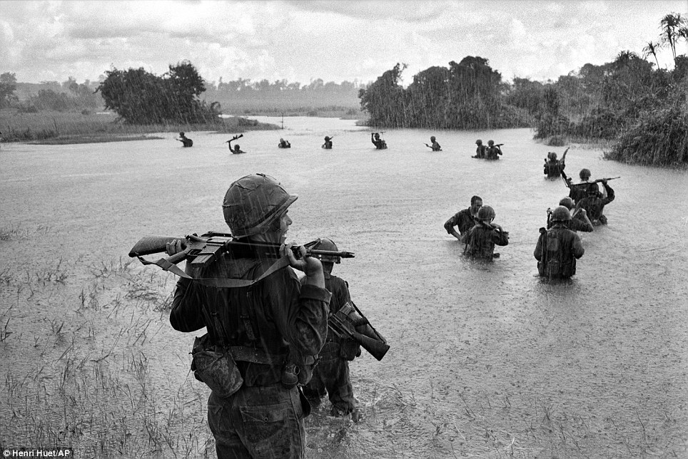 Henri Huet, the French war photographer who took this powerful image, died in 1971 when the helicopter he and three other photojournalists were in was shot down. It shows U.S. paratroopers of the 2nd Battalion, 173rd Airborne Brigade, hold their automatic weapons above water as they cross a river in the rain during a search for Viet Cong positions in the jungle area of Ben Cat, September 25, 1965 Photo courtesy of the dailymail.co.uk