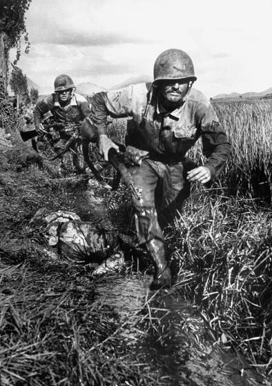 Two U.S. Marines of Co. B, 1st Brigade, 5th Regiment grimly advancing along a ditch past an enemy corpse during the fighting in the Naktong River area in August 1950. Photo by Time war photographer David Douglas Duncan. See more at http://time.com/3783066/david-douglas-duncan-a-life-magazine-war-photographer-looks-back/